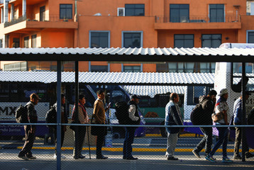 People wait to board a bus after Mexico declared a health emergency and issued stricter rules aimed at containing the coronavirus disease (COVID-19), in Mexico City