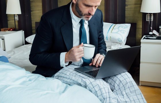 Businessman sitting on the bed with laptop and coffee