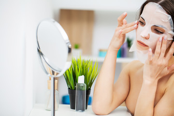 A woman uses a face care mask in the bathroom Wall mural