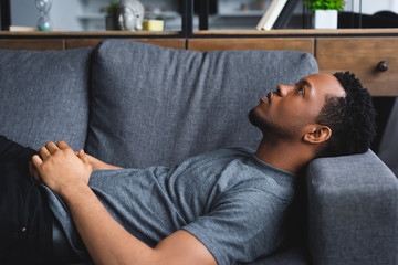 lonely african american man lying on sofa at home
