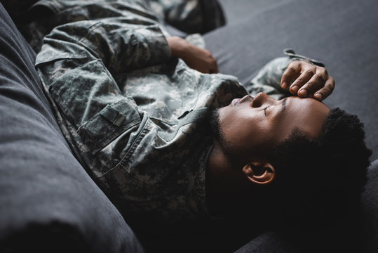 tired african american soldier in military uniform sleeping in sofa at home