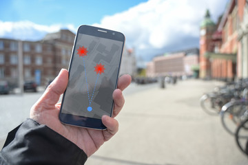 Hand with mobile phone and coronavirus tracking  app against the spread of the pandemic, but...
