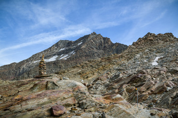 Wall Mural - Small rock tower with majestic peaks in background close to Hohsaas above the Saas-Grund village