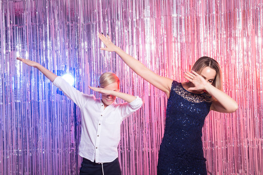 Fun, mothers day, children and family concept - teen boy and his mom funny dancing shiny party background.