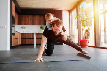 Father working out, doing single arm plank with his jolly baby riding on him