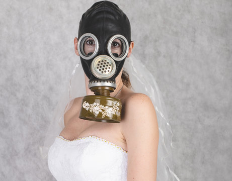 cyberpunk Bride in veil dress and protective gas mask and veil posing.