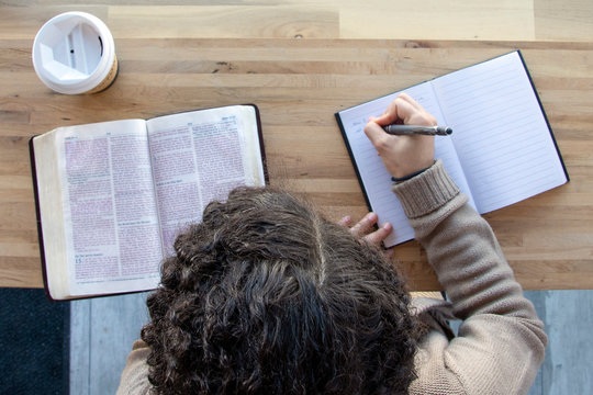 top view of woman journaling as she reads and works on a bible study
