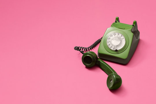 Green vintage antique rotary phone with lifted handset receiver on a pink background with copy space and room for text with a right side composition.