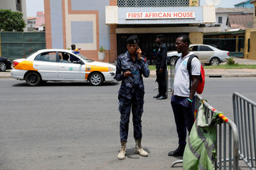 A police officer checks ID at a roadblock to restrict inter-city movement during partial lockdown in the cities of Accra and Kumasi to slow the spread of the coronavirus disease (COVID-19) in Circle, district of Accra