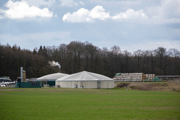 Biogas plant with straw bale stock and smoking chimney on the field at the edge of the forest, cloudy sky, copy space
