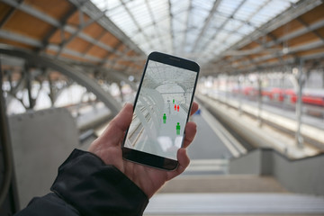 Hand with a smartphone app for tracking the spread of infection which determines the contact persons of people who have been infected with the coronavirus, train station blurry in the background