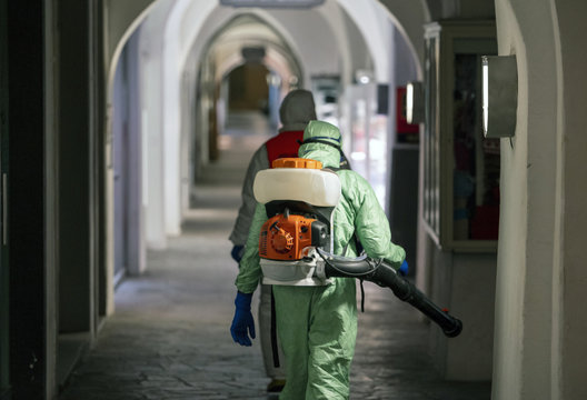 Sanitization, cleaning and disinfection of the streets and alleys in the city center due to the emergence of the Covid-19 virus. Specialized team with protective suits and masks at work in the city.