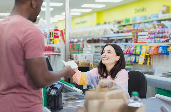 Smiling cashier giving receipt to customer at supermarket checkout