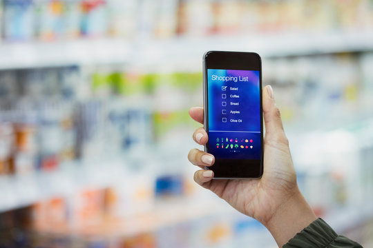 Woman checking digital shopping list on smart phone in supermarket
