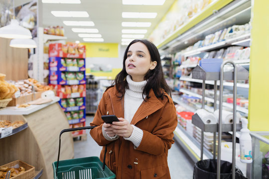 Woman with smart phone shopping in supermarket