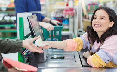 Smiling female cashier receipt to customer at supermarket checkout