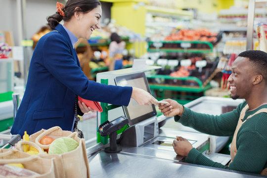 Customer paying cashier at supermarket checkout