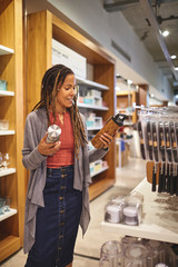 Woman shopping for insulated drink containers in home goods store