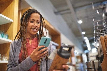 Woman with smart phone shopping in home goods store
