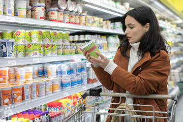 Young woman reading label on container in supermarket