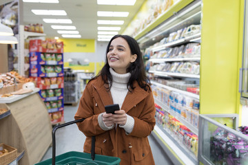 Smiling young woman with smart phone grocery shopping in supermarket