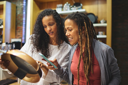 Women friends with smart phone shopping for frying pan