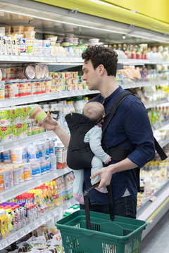 Father with baby daughter grocery shopping in supermarket