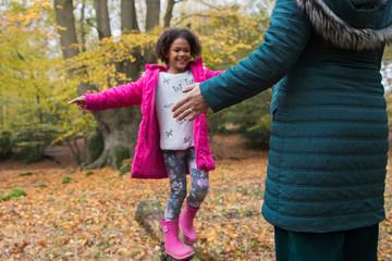 Happy girl balance on fallen log in autumn woods