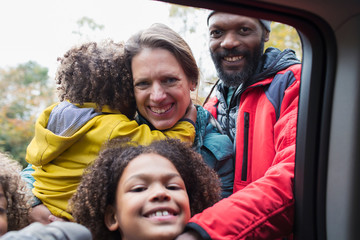 Portrait happy multiethnic family at car window