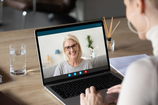 Back view of woman speak talk on video call on computer with smiling elderly mother, young female communicate online using laptop Webcam chat with happy mature mom, quarantine at home