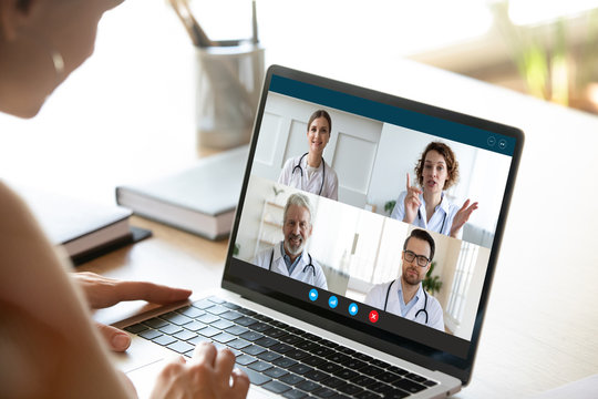 Close up of young female talk on video call consult with diverse doctors colleagues, woman patient have online consultation with GP or physicians, medical nurse in Webcam conference with coworkers