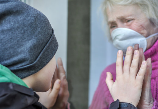 A crying grandmother mature woman in a respiratory mask communicates with grandchild through a window. Elderly quarantined, isolated. Pandemic coronavirus covid-19. Older people. Family values, care