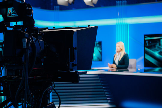 Recording at TV news studio positioned camera equipment with television presenter journalist reporting worldwide.Television announcer during live broadcast streaming.TV director/editor.Mass media