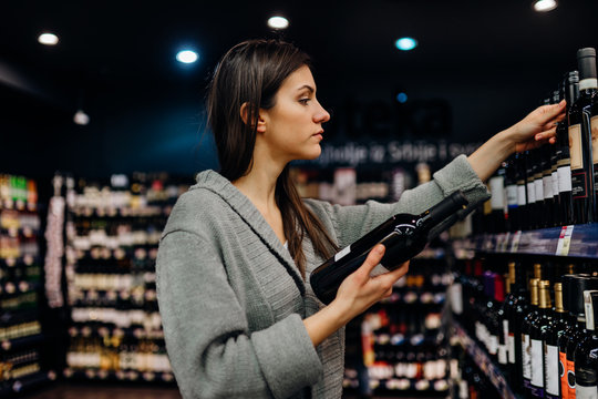 Woman shopping for expensive wine in supermarket alcohol store.Choosing and buying good cheap wine.Benefits of drinking wine.Resveratrol.Everyday binge drinking.Oenology.Mediterranean diet.Alcoholism