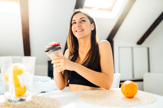 Woman in sportswear drinking sweet orange amino acid powder smoothie after home workout.Keto supplement.After exercise liquid meal.Weight loss fitness nutrition diet post work out.Organic citrus fruit