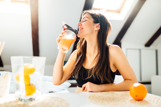 Woman at home drinking orange flavored amino acid vitamin powder.Keto supplement.After exercise liquid meal.Weight loss fitness nutrition diet.Immune system support.Organic citrus fruit.Strong body
