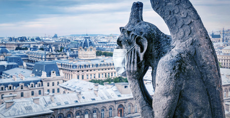 COVID-19 coronavirus in France, medical mask on gargoyle of Notre Dame in Paris. Tourist landmarks closed due to corona virus outbreak.