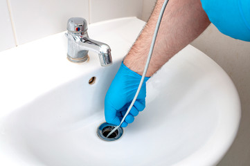Plumbing issues, occupation in sanitation and handyman contractor concept with plumber repairing drain with plumbers snake (steel spiral that twists through pipes to collect dirt) in residential sink
