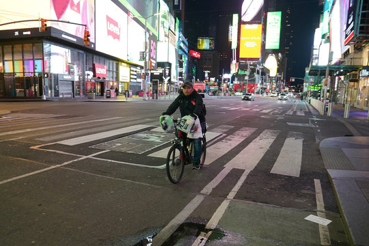 A bicycle delivery person rides his bike through a mostly deserted Times Square during the outbreak of Coronavirus disease (COVID-19), in the Manhattan borough of New York City