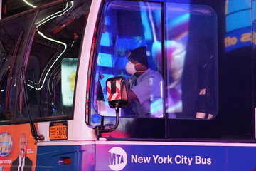 A bus driver wears a mask as he drives though a mostly deserted Times Square during the outbreak of the coronavirus disease (COVID-19), in the Manhattan borough of New York City