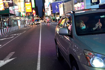 A woman wearing a protective mask takes photos though the window of a vehicle of a mostly deserted Times Square during the outbreak of the coronavirus disease (COVID-19), in the Manhattan borough of New York City