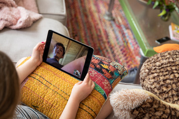 A young girl video chats with her classmates and friends during the Covid-19 pandemic social distancing.