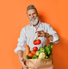 Cool old mature senior man with gray beard shopping hold grocery shopping bag with healthy organic...