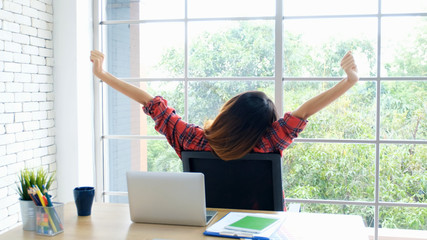 Fototapeta Work from home, Stretch for relax, Young asian woman stretching body while working with laptop computer at her desk home office, Back of female student raised arms take rest from online education obraz