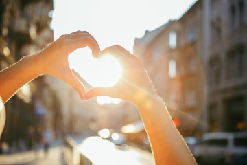 woman hands in heart love shape symbol sunset