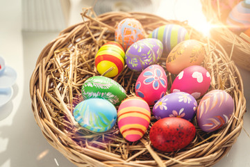 Spoed Fotobehang Tulp close up of many different vibrant colorful piles easter eggs laying on bird nest basket with straw hay, representing decorating and painting eggs to celebrate easter holidays with sunlight reflection
