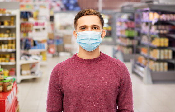 health, safety and pandemic concept - young man wearing protective medical mask for protection from virus over supermarket background