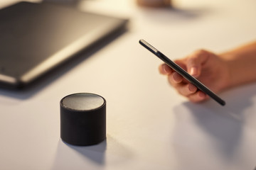 business, technology and internet of things concept - hand with smartphone and smart speaker at night office