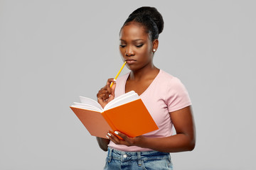 education, school and people concept - african american woman with notebook and pencil over grey background