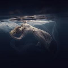 Woman in a sequin dress underwater